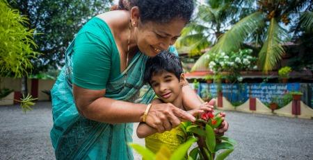 Dame viser liten døvblind gutt en blomst