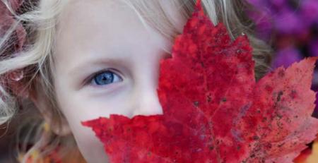 Bilde av jente som holder et stort rødt høstblad foran øye og munn.
